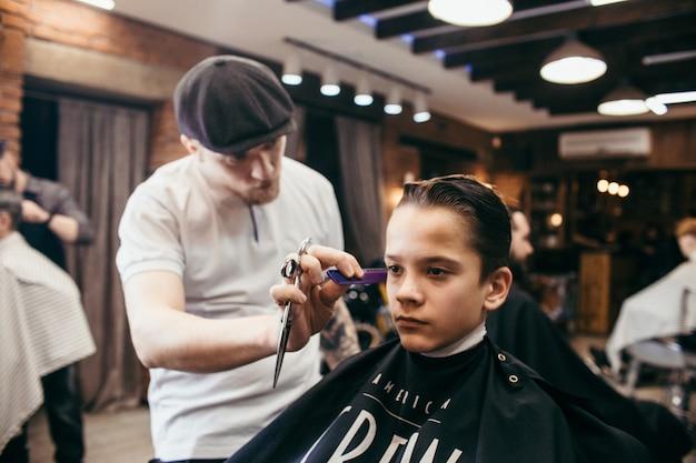 Parrucchiere di tagli di capelli dell'adolescente nel negozio di barbiere. acconciatura retrò alla moda alla moda