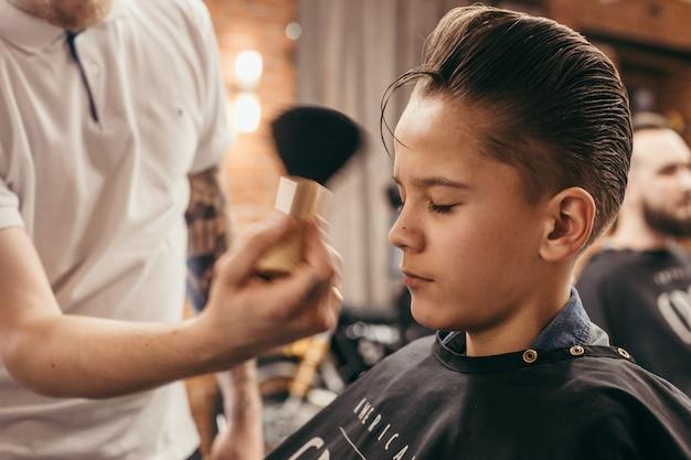 Parrucchiere di tagli di capelli dell'adolescente nel negozio di barbiere