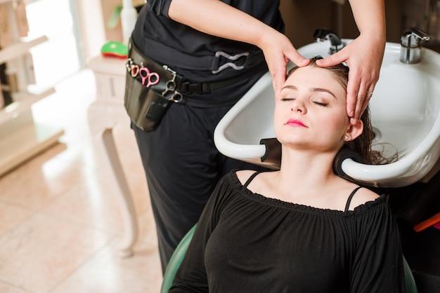 Parrucchiere e donna durante il lavaggio dei capelli