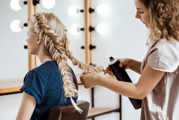 Parrucchiere femminile che fa acconciatura alla donna bionda nel salone di bellezza