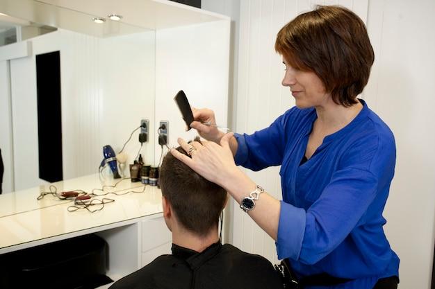 Parrucchiere femminile che taglia i capelli di un giovane ragazzo