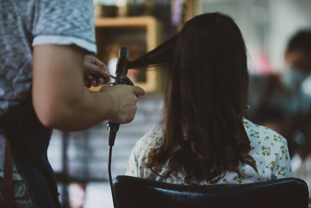 Parrucchiere femminile in piedi, trucco viso e acconciatura per carina adorabile giovane donna nel salone di bellezza