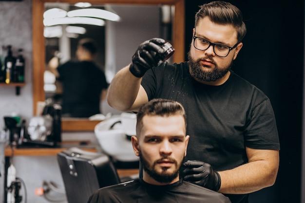 Parrucchiere in un negozio di barbiere che disegna i capelli di un cliente