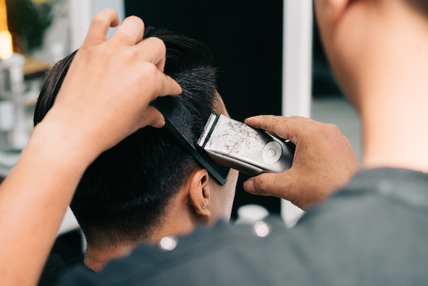 Parrucchiere irriconoscibile che taglia i capelli del cliente con rifinitore e pettine