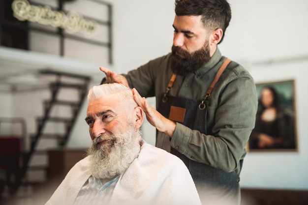 Parrucchiere maschio che lavora con i capelli del cliente invecchiato