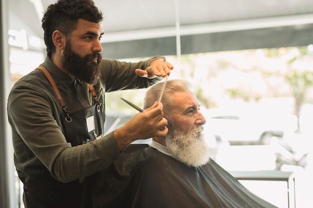 Parrucchiere maschio che pettina i capelli del cliente anziano nel parrucchiere