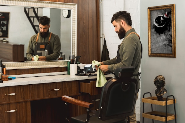Parrucchiere maschio che prepara gli strumenti per lavoro nel negozio di barbiere