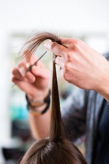Parrucchiere maschio che taglia i capelli della donna nel negozio di parrucchiere