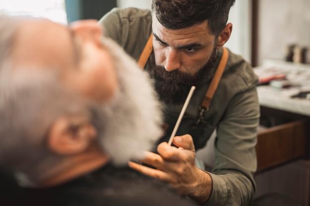 Parrucchiere maschio dei pantaloni a vita bassa che lavora con la barba del cliente senior