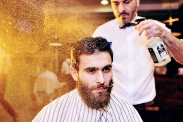 Parrucchiere o barbiere spruzza acqua sui capelli del cliente nel moderno barbiere