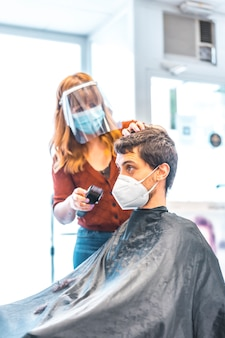 Parrucchiere, pandemia di coronavirus, covid-19. misure di sicurezza, maschera, schermo protettivo, distanza sociale. tagliare i capelli di un giovane dopo la quarantena con un rasoio, foto verticale