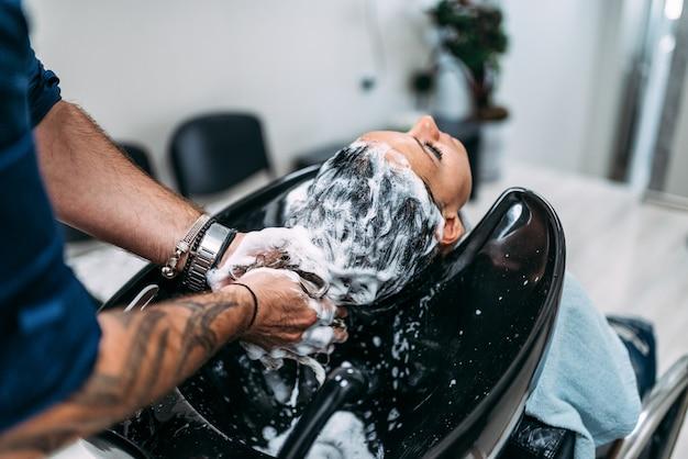 Parrucchiere professionista che lava i capelli ai clienti. avvicinamento.