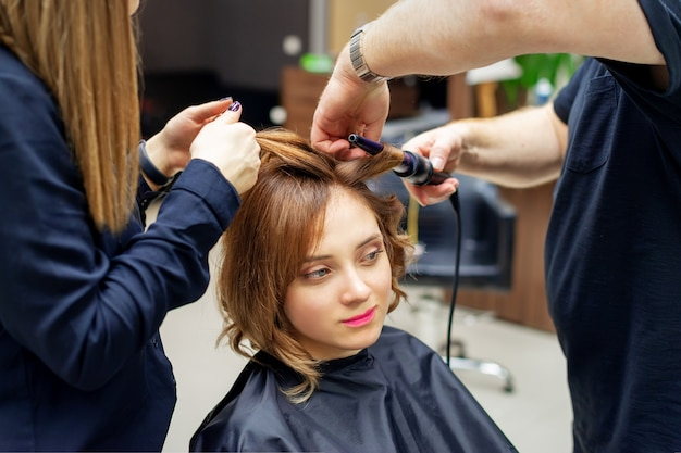 Parrucchiere professionista colpi di scena riccioli di lunghi capelli castano chiaro di donna con ferro arricciacapelli nel salone di bellezza. procedure di parrucchiere