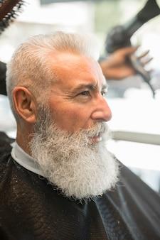 Parrucchiere senza volto che rende i capelli lo styling cliente maschio