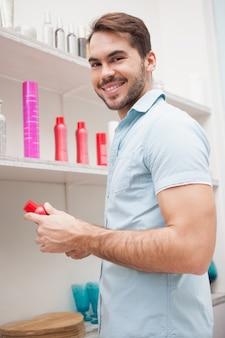 Parrucchiere sorridente con prodotti per i capelli