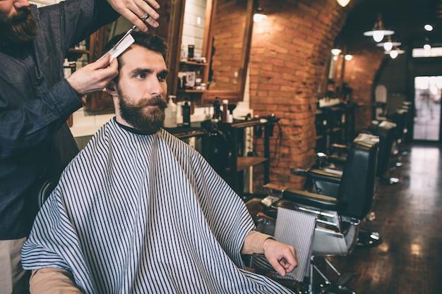 Parrucchiere sta tagliando i capelli del suo cliente. lo sta facendo molto preciso e tenero. il cliente è seduto su una sedia. lui è molto serio.
