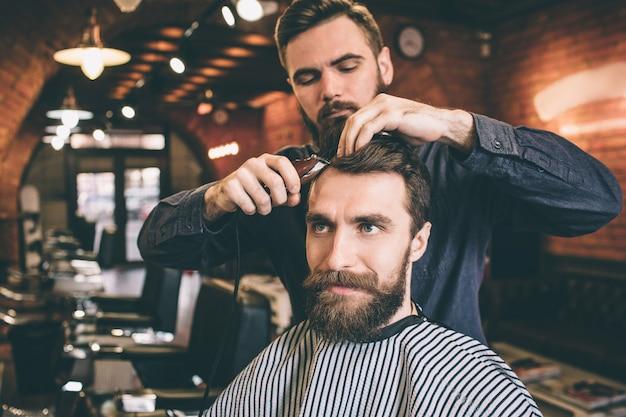 Parrucchiere usa le forbici per tagliare i capelli. lo sta facendo molto accuratamente. il cliente guarda avanti e sorride.