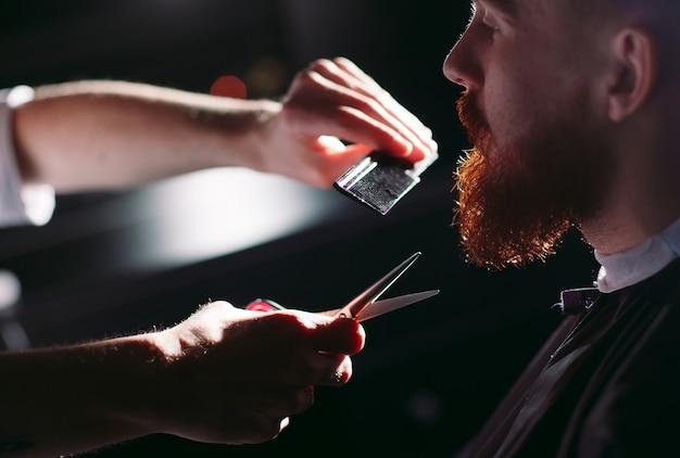 Parrucchiere visita uomo sicuro nel negozio di barbiere.