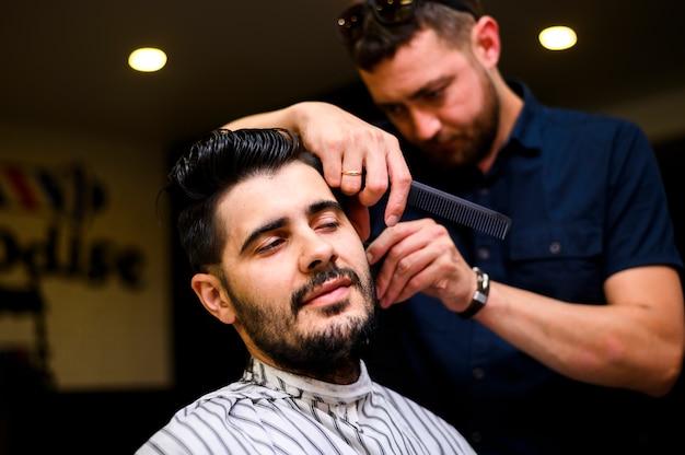 Parrucchiere vista frontale che taglia i capelli del cliente