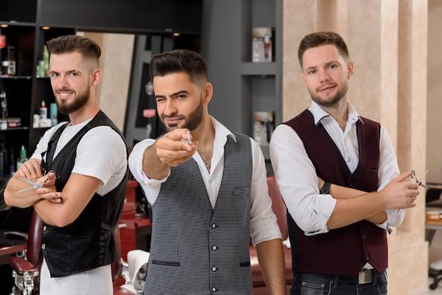 Parrucchieri in posa, barbiere barbuto che punta con le forbici alla macchina fotografica e ammiccanti.