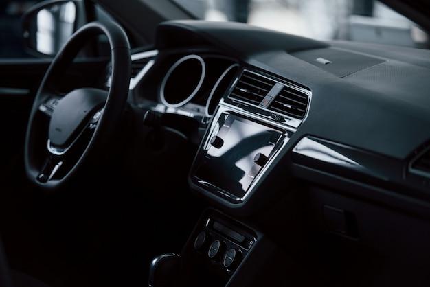 Parte anteriore dell'automobile nuova di zecca. interni neri moderni. concezione dei veicoli