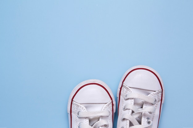 Parte anteriore delle scarpe dei bambini su un fondo blu. copia spazio per testo su scarpe, vestiti, passeggiate per bambini.