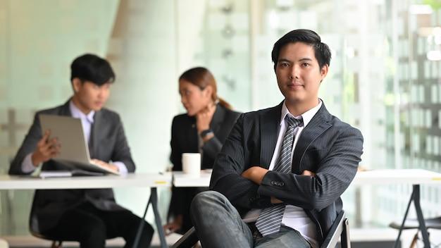 Parte anteriore di seduta del giovane uomo d'affari con confidenza della sala riunioni.