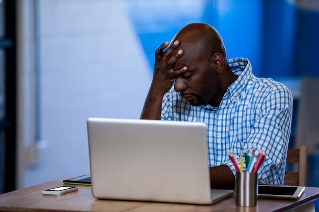 Parte anteriore infastidita dell'uomo d'affari del suo computer portatile