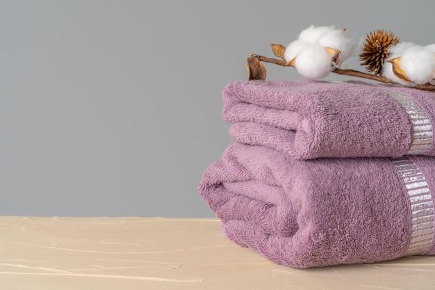 Parte anteriore morbida degli asciugamani di cotone sulla tavola di legno