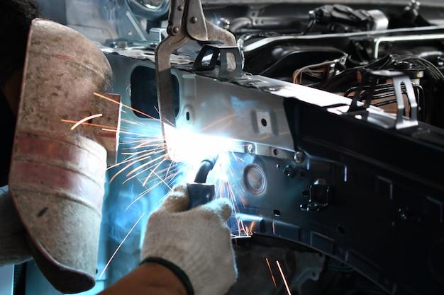 Parte automobilistica del saldatore degli uomini - officina riparazioni auto
