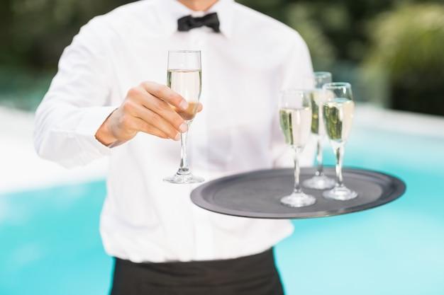 Parte centrale del cameriere che offre champagne