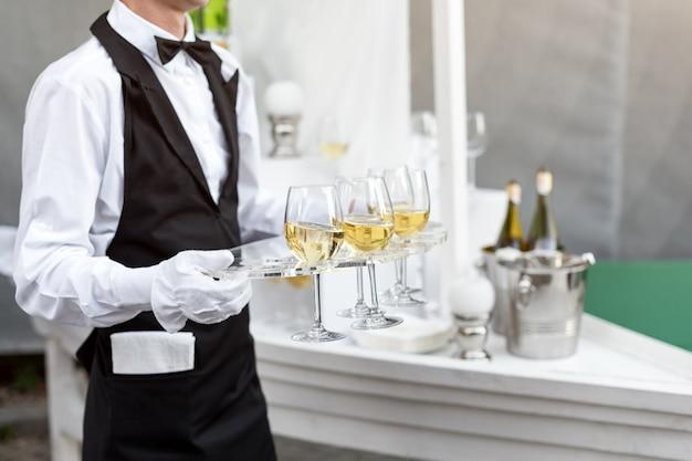 Parte centrale del cameriere professionista in uniforme che serve vino durante la festa di catering a buffet, eventi festivi o matrimoni. bicchieri pieni di champagne sul vassoio. servizio di catering per feste all'aperto, cameriere di turno.