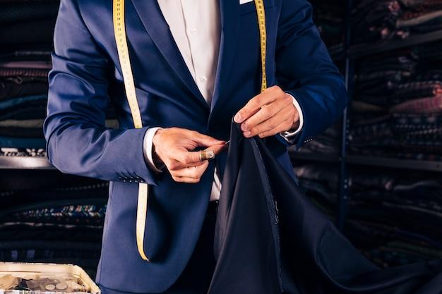 Parte centrale di un designer di moda maschile che cucisce il tessuto con l'ago