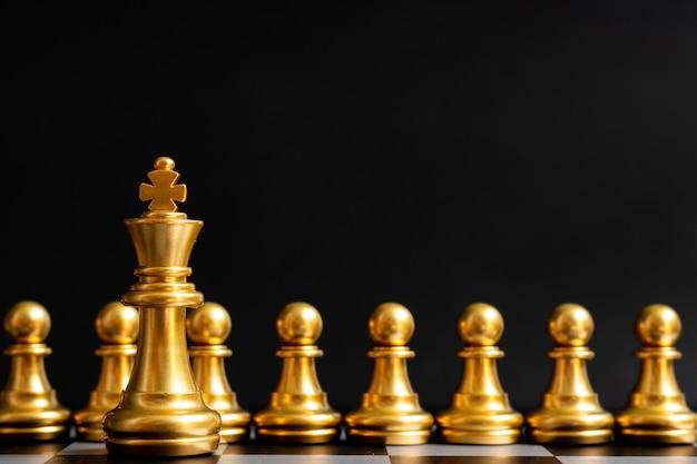 Parte del pezzo degli scacchi re d'oro davanti al pedone sul nero (concetto di leadership, gestione)