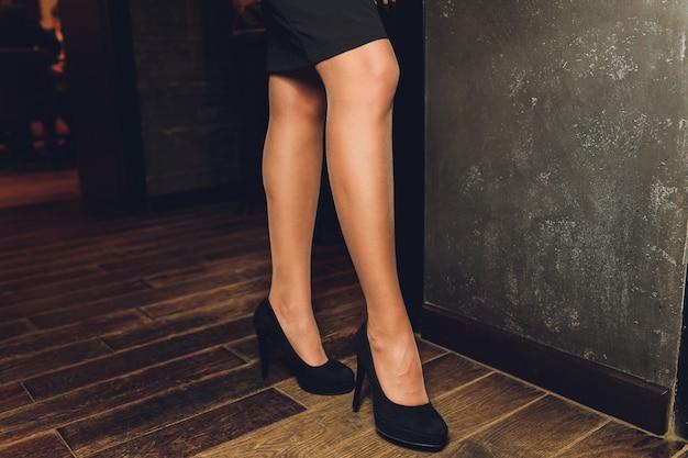 Parte di giovani donne con gambe perfette mantenendo le gambe incrociate al ginocchio mentre era seduto sul divano presso il negozio di scarpe.