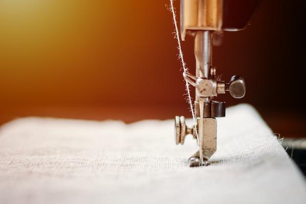 Parte di una macchina da cucire vintage e capo d'abbigliamento. ago in acciaio con crochet e primo piano del piedino premistoffa.