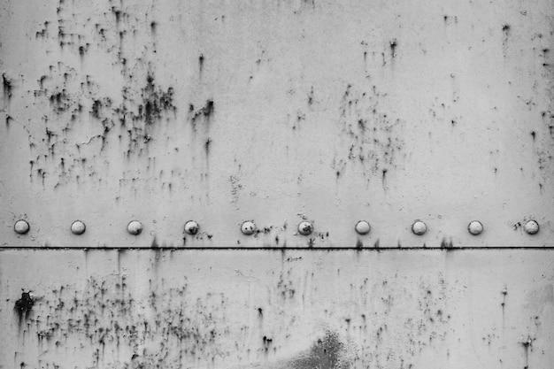 Parte posteriore astratta del fondo e lamiera di acciaio bianca con ruggine, parete del treno vecchia ed arrugginita