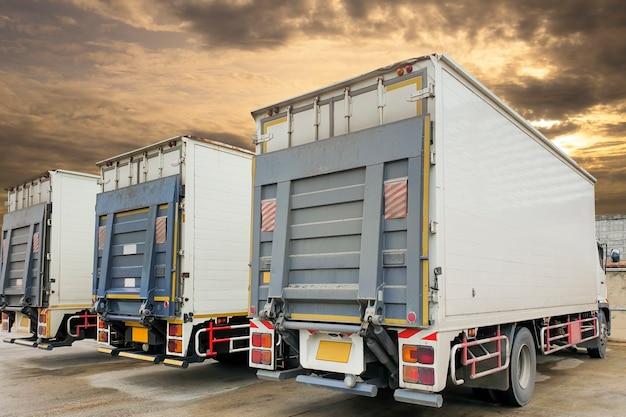 Parte posteriore del container camion con parcheggio dell'ascensore idraulico a magazzino, logistica del settore merci e trasporti