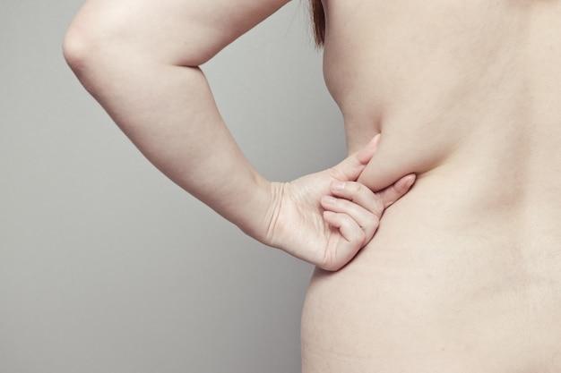 Parte posteriore del corpo umano con pieghe sul retro. malnutrizione e bassa attività atletica. concetto di obesità e golosità