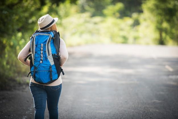 Parte posteriore del viaggiatore con zaino e sacco a pelo della giovane donna che cammina sul sentiero nel bosco e sulla visualizzazione della natura intorno.