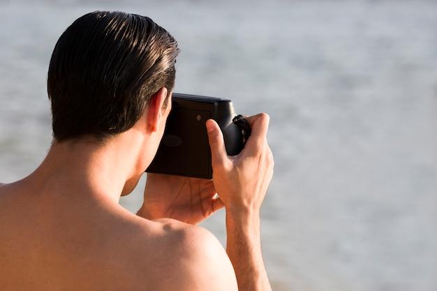 Parte posteriore dell'uomo che prende immagine dalla macchina fotografica istantanea sulla spiaggia