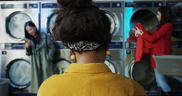 Parte posteriore della donna alla moda afroamericana nella stanza di servizio della lavanderia. clienti femminili di razza mista di piccoli lavatoi. punto di vista posteriore sulla ragazza che si siede e che aspetta mentre lavatrici che lavorano e che puliscono i vestiti
