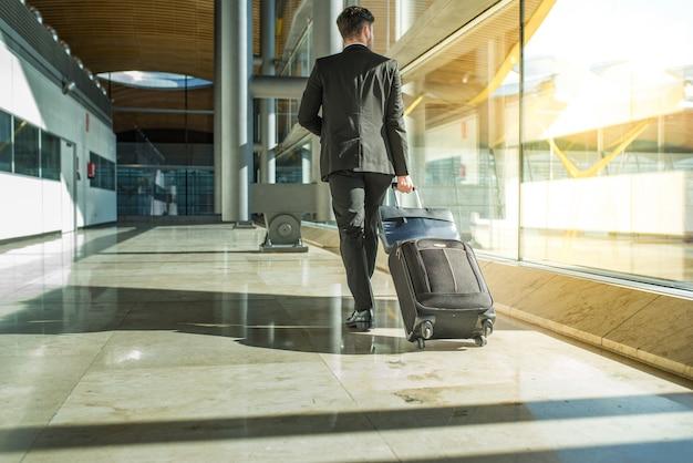 Parte posteriore e gambe dell'uomo d'affari che camminano con i bagagli all'aeroporto
