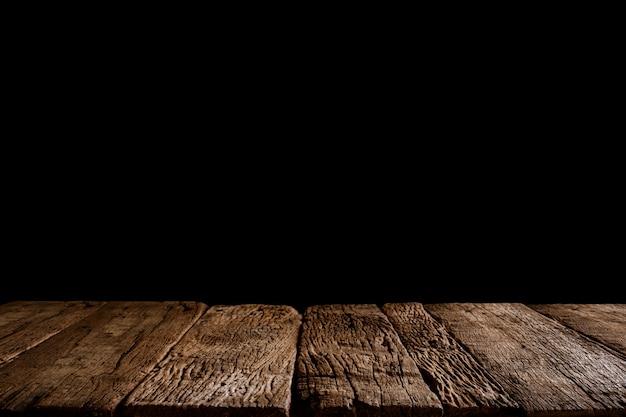 Parte superiore del tavolo di legno vuoto pronto per l'esposizione o il montaggio del prodotto. sfondo nero