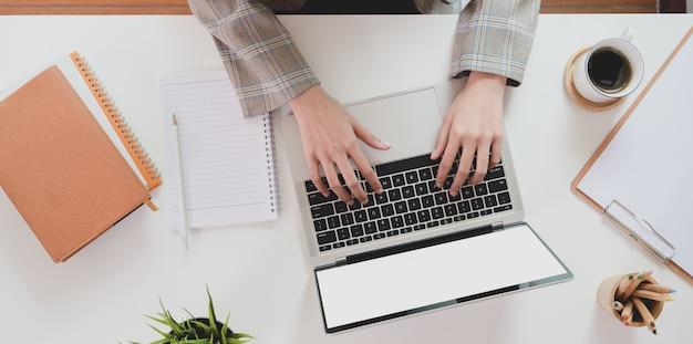 Parte superiore della mano della donna di affari che scrive sul computer portatile