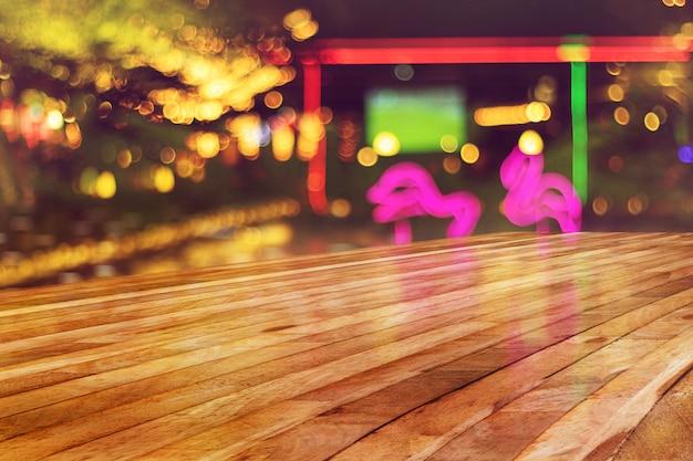 Parte superiore della tabella di legno vuota con luce sfocatura dello sfondo discoteca