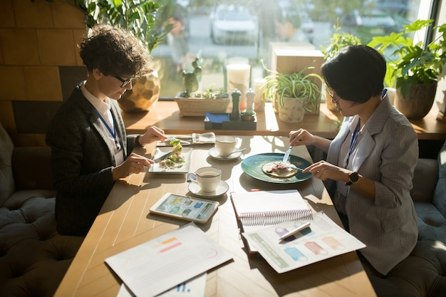 Partecipanti alla conferenza seri che mangiano insalata nel caffè