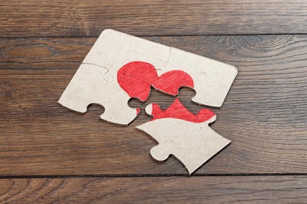 Parti del puzzle formano il cuore, spezzato.