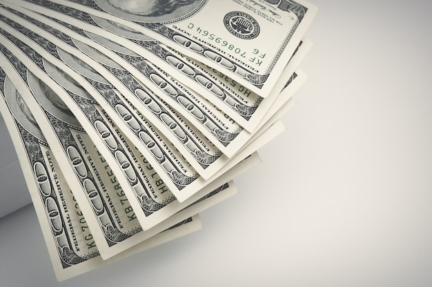 Parti delle banconote da cento dollari si trovano sulla sinistra con un ventilatore.