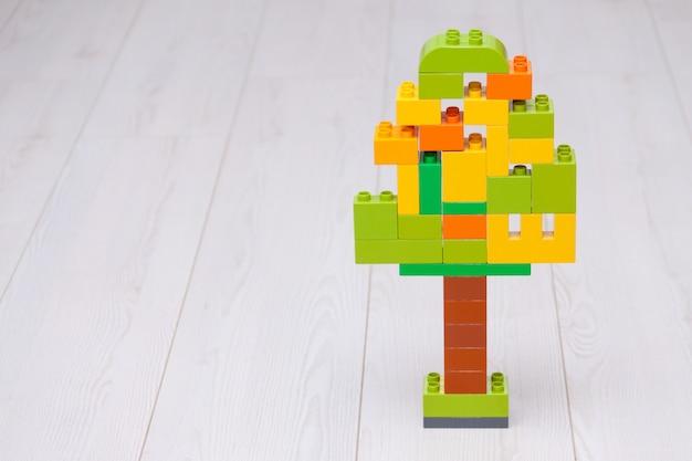 Particelle elementari di plastica multicolori a forma di albero su sfondo chiaro.